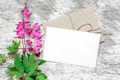 Carte de voeux et enveloppe blanches vides avec le bouquet rose de wildflowers Photo stock