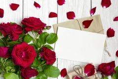 Carte de voeux et enveloppe vides avec des fleurs, des pétales et le boîte-cadeau de roses rouges Photos libres de droits