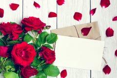 Carte de voeux et enveloppe vides avec des fleurs et des pétales de roses rouges Images libres de droits