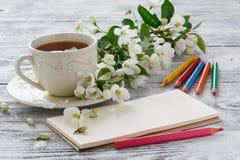 Carte de voeux et tasse vides de thé vert de fleur avec des branches de cerise de floraison sur le fond en bois rustique blanc Images libres de droits