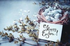 Carte de voeux heureuse de Pâques avec le lettrage, nid avec des oeufs d'oiseau et des brindilles et des fleurs de ressort Photographie stock