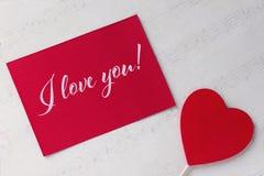 Carte de voeux de jour de valentines avec le fond rouge et le lettrage de livre blanc de coeur Images libres de droits