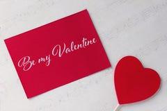 Carte de voeux de jour de valentines avec le fond rouge et le lettrage de livre blanc de coeur Images stock