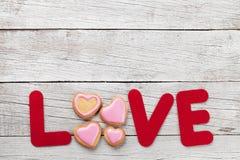 Carte de voeux de jour de valentines avec le mot et les biscuits d'amour Photographie stock