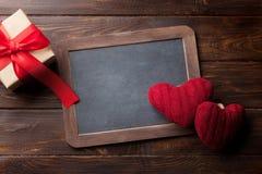 Carte de voeux de jour de valentines avec les coeurs et le cadeau rouges Photo stock
