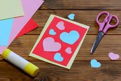 Carte de voeux de jour de valentines avec les coeurs de papier, ciseaux, bâton de colle, feuilles de papier sur un fond en bois Image stock