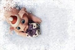 Carte de voeux de Noël - porc rose doux avec le cadeau dans le cadre des flocons de neige blancs photo libre de droits