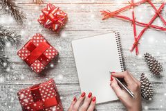 Carte de voeux de Noël, sur le fond en bois blanc, les cadeaux faits main, les branches et les cônes de sapin, étoile rouge Photo libre de droits