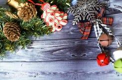 Carte de voeux de Noël sur les boules en bois de Noël de fond et guirlande avec l'arbre de Noël vert cloches de branche Images stock
