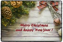 Carte de voeux de Noël sur les boules en bois de Noël de fond et guirlande avec l'arbre de Noël vert cloches de branche Photographie stock libre de droits