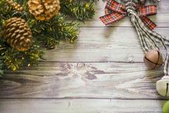 Carte de voeux de Noël sur les boules en bois de Noël de fond et guirlande avec l'arbre de Noël vert cloches de branche Photographie stock