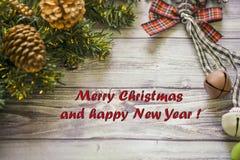 Carte de voeux de Noël sur les boules en bois de Noël de fond et guirlande avec l'arbre de Noël vert cloches de branche Photos libres de droits