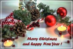 Carte de voeux de Noël sur les boules en bois de Noël de fond et l'arbre de Noël vert de branche avec des cônes de pin, bougie Photographie stock
