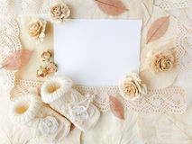 Carte de voeux nouveau-née ou de baptême Papier blanc avec des chaussures de bébé sur le fond de biege Configuration plate Vue su Image stock