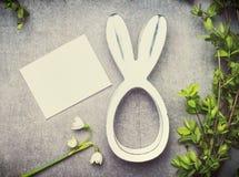 Carte de voeux de Pâques avec des fleurs du muguet, des brunchs verts et le décor de lapin Photographie stock libre de droits