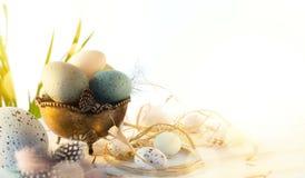 Carte de voeux de Pâques avec les oeufs de pâques colorés et flowersl de sprin sur la table bleue image libre de droits