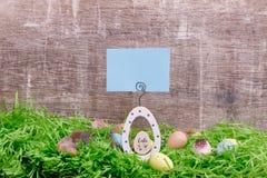 Carte de voeux de Pâques et oeufs de caille sur une herbe verte devant un fond en bois Copiez l'espace Image libre de droits
