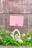 Carte de voeux de Pâques et oeufs de caille sur une herbe verte devant un fond en bois Copiez l'espace Photographie stock libre de droits