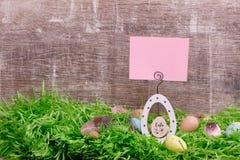 Carte de voeux de Pâques et oeufs de caille sur une herbe verte devant un fond en bois Copiez l'espace Photo stock