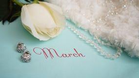 Carte de voeux, rose de blanc, bijoux et velours sur un fond bleu Photographie stock libre de droits