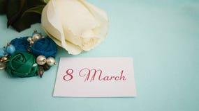 Carte de voeux, rose de blanc, boucles d'oreille et broche sur un fond bleu Photographie stock libre de droits
