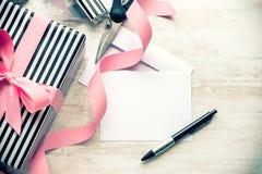 Carte de voeux vide Cadeau et matériaux d'emballage enveloppés sur un fond en bois blanc Type de cru Images libres de droits