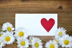 Carte de voeux vierge avec le coeur sur lui et des marguerites Image stock