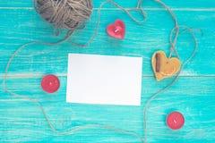Carte de voeux vierge ouverte sur un fond minable en bois bleu avec le coeur, les bougies et un écheveau de fil Maquette Images stock