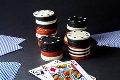 Carte della mazza e lotto dei chip sopra il nero Coppie re shallow fotografie stock