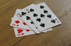 Carte della mazza su un backround di legno, sull'insieme dei nines dei club, sui diamanti, sulle vanghe e sui cuori Immagini Stock Libere da Diritti