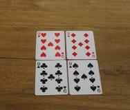 Carte della mazza su un backround di legno, sull'insieme dei nines dei club, sui diamanti, sulle vanghe e sui cuori Immagine Stock