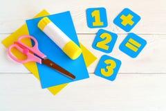 Carte di carta con i numeri, forbici, strati di carta, colla su un fondo bianco Concetto di formazione Fotografia Stock Libera da Diritti