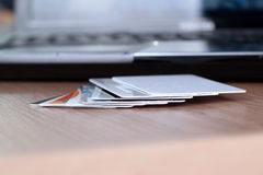 Carte di credito su una tavola e su un computer portatile dietro Immagini Stock Libere da Diritti