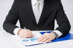 Carte di lavoro e di firma dell'uomo d'affari Immagine Stock