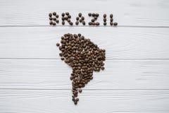 Carte du Brésil fait de grains de café rôtis s'étendant sur le fond texturisé en bois blanc Images stock