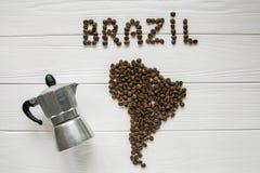 Carte du Brésil fait de grains de café rôtis s'étendant sur le fond texturisé en bois blanc avec le fabricant de café Photographie stock libre de droits