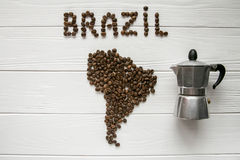 Carte du Brésil fait de grains de café rôtis s'étendant sur le fond texturisé en bois blanc avec le fabricant de café Image stock