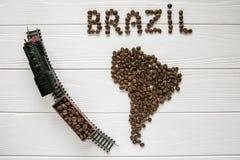Carte du Brésil fait de grains de café rôtis s'étendant sur le fond texturisé en bois blanc avec le train de jouet Photos libres de droits