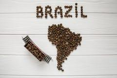 Carte du Brésil fait de grains de café rôtis s'étendant sur le fond texturisé en bois blanc avec le train de jouet Photo libre de droits