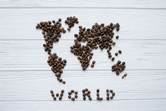 Carte du monde fait de grains de café rôtis s'étendant sur le fond texturisé en bois blanc avec la signature et l'espace pour le  Photo stock