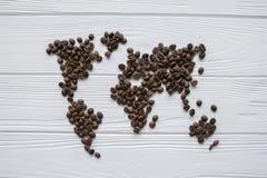 Carte du monde fait de grains de café rôtis s'étendant sur le fond texturisé en bois blanc avec le ` de ` de signature bonjour Photographie stock libre de droits