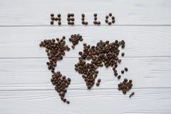 Carte du monde fait de grains de café rôtis s'étendant sur le fond texturisé en bois blanc avec le ` de ` de signature bonjour et Photographie stock libre de droits