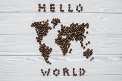 Carte du monde fait de grains de café rôtis s'étendant sur le fond texturisé en bois blanc avec le ` du monde de ` de signature b Photographie stock