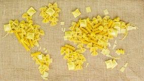 Carte du monde fait de pâtes crues sur le fond de tissu Photo stock
