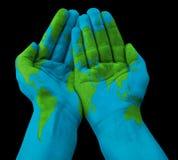 Carte du monde peinte sur les mains humaines Image libre de droits