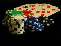 Carte e chip di gioco sui precedenti neri Fotografia Stock