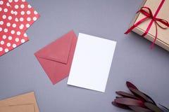 Carte et cadeau actuels dans la boîte avec le ruban de satin sur le fond gris image libre de droits