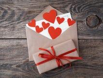 Carte et coeurs rouges dans l'enveloppe ouverte du papier d'emballage brun GIF Image stock