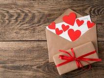Carte et coeurs rouges dans l'enveloppe ouverte du papier d'emballage brun GIF Images stock