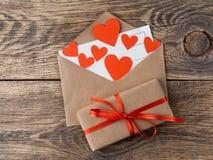 Carte et coeurs rouges dans l'enveloppe ouverte du papier d'emballage brun GIF Photographie stock